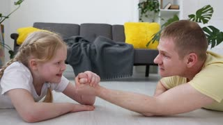 happy modern family. Dad and his little daughter are measured by force on the floor in the living room.