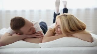 Happy young couple in love laying on the bed