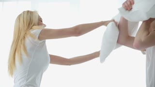 Happy young loving couple fights pillows in the bedroom