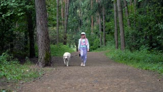 little girl is walking with a dog in the forest