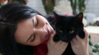 love for pets. beautiful dark-haired girl with a black cat is relaxing at home in the bed room