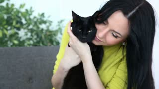 love for pets. beautiful dark-haired girl with a black cat is relaxing at home in the living room on the couch.