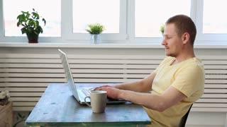 man freelancer working remotely at home on laptop