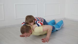 modern healthy family. Dad and his young son go in for sports at home.
