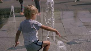 modern life in a big world - children have fun running around the city fountain