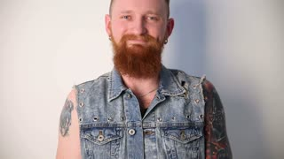 modern youth. a cheerful portrait of a kindly smiling biker with tattoos and a stylish beard and mustache in a denim vest.