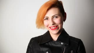 modern youth. portrait of a laughing woman of unusual appearance with red hair and creative hairstyle in a leather jacket.