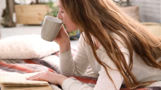 woman drinks coffee and reads book in bed bedroom