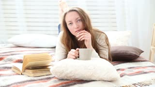 woman drinks coffee in bed bedroom