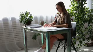 work at home. young beautiful freelancer woman is working at the table by the window in the house. modern ecological interior with living plants.