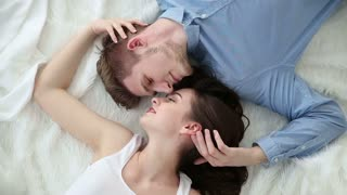 Young loving couple lying on bed at home