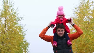 young Dad with a small child having fun in autumn park - closeup, handheld shot