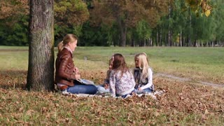 young woman at work as educator reading book to girls in park