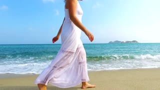 Girl in white dress walking on the sand beach on sunny day. Slow motion.