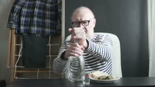 an elderly man, a sailor retired drinking alcohol