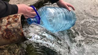 man picks up water from a spring in a plastic bottle