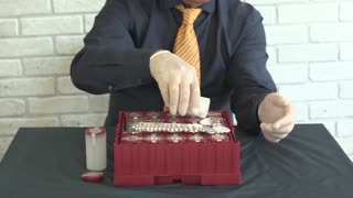 man with a container of silver coins