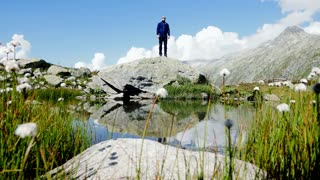 adventure achievement of young male hiker standing on top of mountain lake