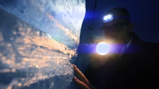 adventure background of person using flashlight to discover ice glacier cave