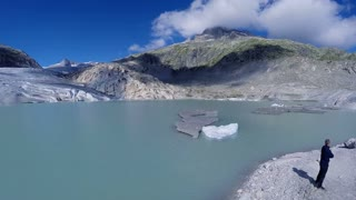 aerial view of man standing in front of glacier lake looking at landscape