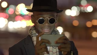 african american man using smart phone in the city at night