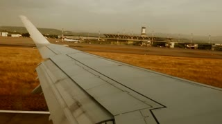 airplane landing. arriving at airport. aircraft wing. runway. window view