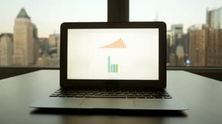 analyzing charts and diagrams on laptop computer screen. financial business desk