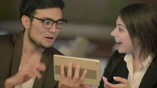 asian man talking with white women looking at tablet computer