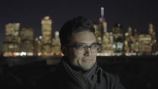 asian man with glasses standing outdoors in the city at night using tablet pc