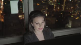 attractive sales women working on pc in modern city office at night