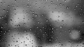 black and white background of rain drops on glass window front