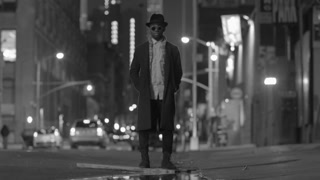 black and white scene of man standing on city street at night