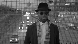 black man standing on bridge road in the city