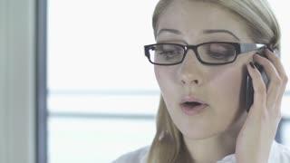 blond busyness talking on phone. tracking shot. eyeglasses secretary