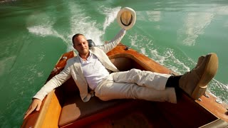 boat ride in slow motion. young casual man relaxing. white suit cloth