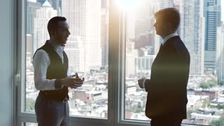 business meeting scene of two businessman analyzing charts and diagrams
