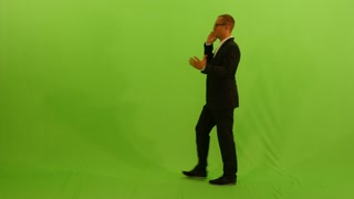 businessman walking and talking on the phone. isolated green screen