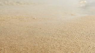 close up of beach sand. beach waves background
