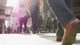 close up of walking feet crossing street in the city
