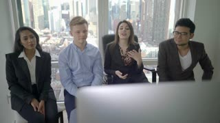 diverse multi ethnic group of young business people looking at computer screen