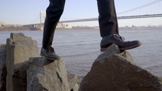 feet walking over stone rocks overcoming obstacles shot in slow motion