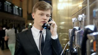 frustrated young man talking in phone booth getting bad news