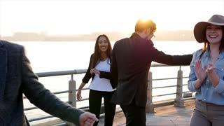 group of happy young friends dancing cheerful outdoors at sunset in slow motion