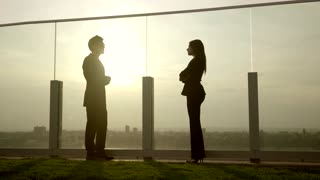 group of two young successful business people meeting on rooftop at sunset