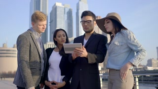 group of young friends looking at tablet computer outdoors