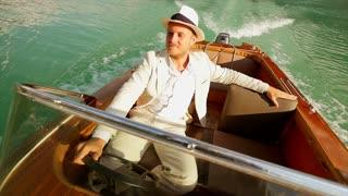 happy man enjoying life ridding boat over lake. raised hands. carefree happiness