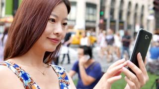happy young women using smart phone. city people background