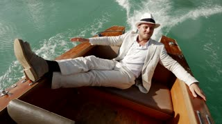 hats off. young caucasian man relaxing on boat deck wearing white casual suit