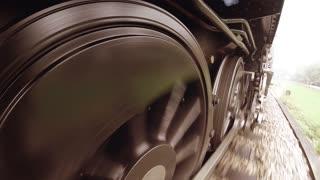 historical steam engine train driving on railroad. nostalgic industrial locomotive background