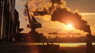 industrial background. smog pollution smoke. cranes. sunset sun flare
